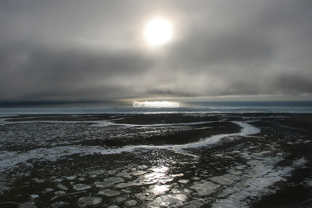 Ariel view near Barrow of the flooded tundra with the never setting sun shining through fog that sits on the Arctic Ocean. (Steve Ringman / The Seattle Times)