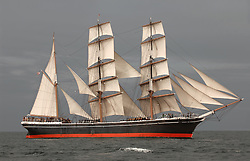 Vintage windjammer tall ship with full sails against a dark gray sky and sea