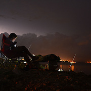 Gary Cosby Jr./Decatur Daily  Kim Taylor checks her cell phone as she sits on the bank of the Tennessee River in Decatur, Ala., Monday night June 9, 2014 as she fishes while a thunderstorm approaches from the west.  The storm brought high wind, heavy rainfall and lightning as it passed through the area.