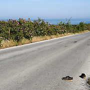 A pair of shoes left on the road between Mantamado and Mytilini. Most refugees land on the northern shores of the island and they walk for nine hours either to Mytilini port or to Moria  First Reception Centre..Everyday hundreds of refugees, mainly from Syria and Afghanistan, are crossing in small overcrowded inflatable boats the 6 mile channel from the Turkish coast to the island of Lesbos in Greece.