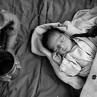 Mehmooda looks at her new baby brother while the baby takes a nap on the floor of their tent. Having lost everything in the flood, the family has no bed and all sleep on the floor. The conditions for the family and newborn are harsh and already a week after delivery the baby suffered a chest infection and had difficulty breathing. Karachi, Pakistan, 2010