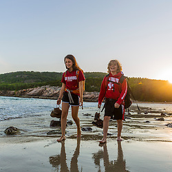 A teenage boy and girl walk on Sand Beach after a hike in Maine's Acadia National Park.