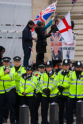 Whitehall, London, April 4th 2015. As PEGIDA UK holds a poorly attended rally on Whitehall, scores of police are called in to contain counter protesters from various London anti-fascist movements. PICTURED: Completely surrounded by a wall of police officers for their own protection, PEGIDA rally attendees wave their flags.