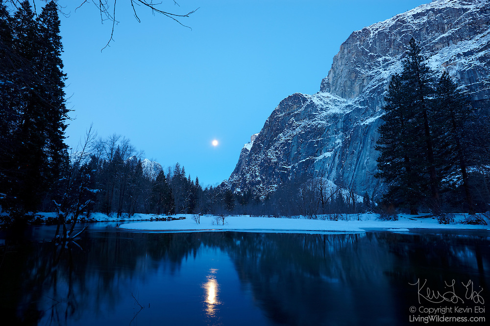 The full moon is reflected in the Merced River at the base of the Lower Brother in Yosemite National Park, California.