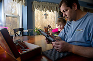 Permitted gun owner Shane Gazda displays his gun collection as his daughter Savannah, 3, looks on at the kitchen table of their  home in Clayton, North Carolina, February 2, 2012. Gazda plans for both his son and daughter to take classes and eventually become permitted gun owners. The North Carolina House Bill 650, which went effect on December 1, 2011, allows concealed weapons in public parks. It also allows local governments to regulate concealed weapons in certain recreational areas such as athletic fields through city ordinances.  Ann Hermes/© The Christian Science Monitor 2012