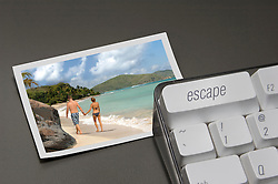 """close up of """"escape"""" key on a computer keyboard with a photo of a tropical paradise next to it"""