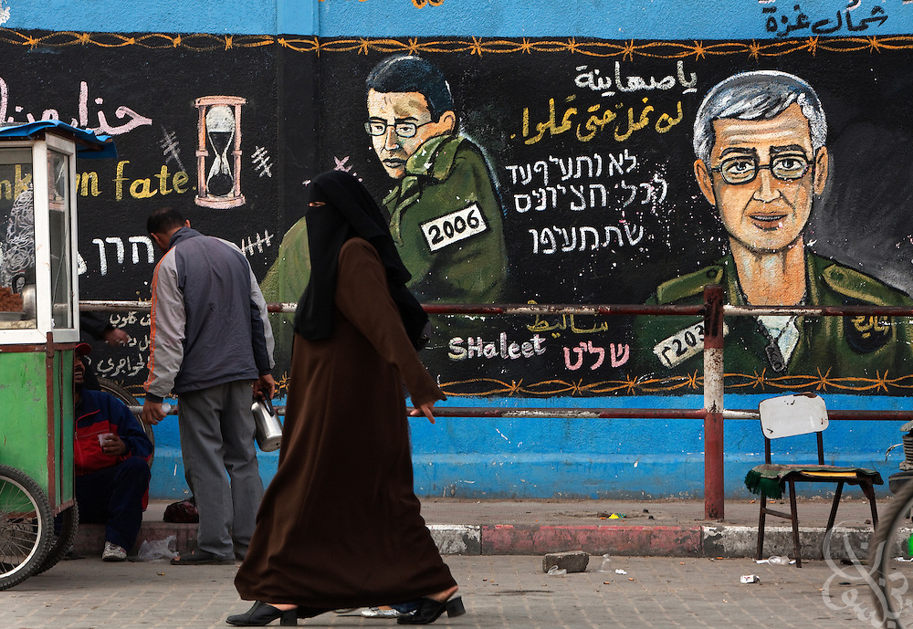 A Palestinian woman walks past a HAMAS mural depicting captive Israeli soldier Gilad Shalit December 26, 2009 in the Jabaliyah Refugee Camp in Gaza.  HAMAS and Israel are reported to have been recently negotiating a prisoner exchange that would see some 950 Palestinian prisoners swapped for Shalit, who has been kept captive for more than 3 years now in Gaza.