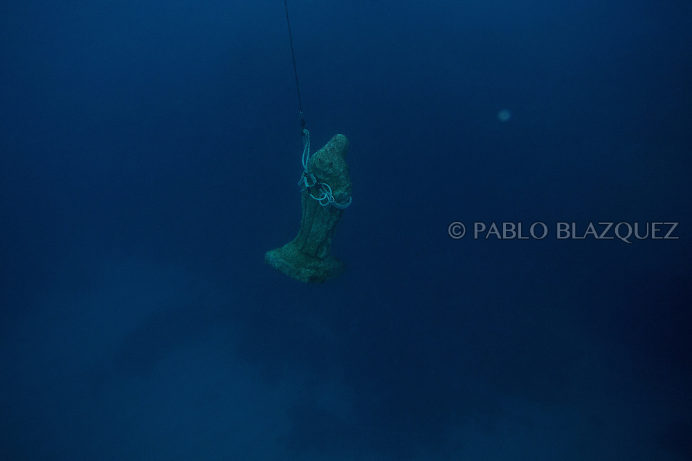 15/08/2016. An image of the Virgin of Palm is hold by a string as divers take it to the surface during the yearly Virgin of Palm maritime pilgrimage on August 15, 2016 in Algeciras, Spain. The Our Lady of Palm maritime pilgrimage in Algeciras dates back to 1975 and takes place annually when fishermen rescue the submerged virgin from the deep sea. Worshippers amid thousands of visitors await its arrival at the Rinconcillo beach. The devotion for the Virgin of Palm comes from the seventeenth century when a ship coming from Italy docked at Algeciras port to wait out bad weather. According to legend, once the crew of the ship removed a box with an image of the Virgin from its cargo the weather turned and the sea's tides were calmed. (© Pablo Blazquez)