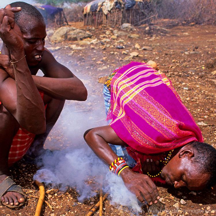 Africa, Kenya. Two Maasai males demonstrate fire starting