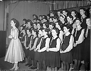 20/03/1959<br /> 03/20/1959<br /> 20 March 1959<br /> Gael Linn singing competition and concert at Dungannon, Co. Tyrone. Image shows Abbey Actress and Singer Aine Nic Chana ? singing with a schoolgirls choir at the concert in St. Patrick's Hall.