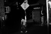 A man walks past the closed entrance to the Kosciuzko Street J train on Broadway in Bushwick, NY.