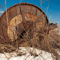 Rusted concrete and iron roller in a snow-covered field.