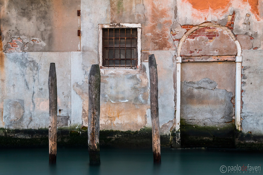 Three wooden poles in front of the facade of an old buiding on a canal in the sestiere (district) of Cannaregio in Venice, Italy