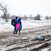 After crossing the Macedonian-Serbian border, refugees walk the unofficial refugee route in subfreezing snowy weather. Near Miratovac, Serbia, January 17, 2016. <br /> <br /> According to UNHCR, 67,415 refugees landed in Greece in January 2016 alone, most of who traveled the route through Serbia on their way to Western Europe. The number of refugees arriving in Greece has dropped significantly since the Balkan border closures in March 2016.<br /> <br /> On assignment for Mercy Corps, I documented refugees crossing through Serbia in January 2016.