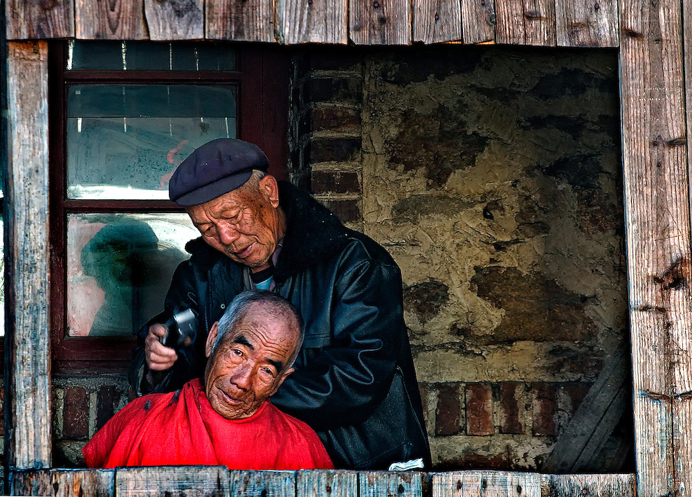A barber and his client in Yuanyang, Yunnan, China