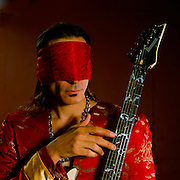 Steve Vai during the G3 tour in a red silk dragon jacket, blindfolded with a red silk scarf holding his Ibanez electric guitar