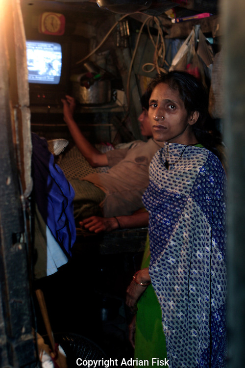 """35 yr old Khatum stands in her tiny home on 21st Oct 2006. It measures approx 6"""" x 12"""", she shares it along with her husband and six children. She describes her life as impossible, the money she gets from her husband, a shoe seller, is barely enough to survive on. Although some Dharavi resisdents have better sized homes for most there is barely enough room."""