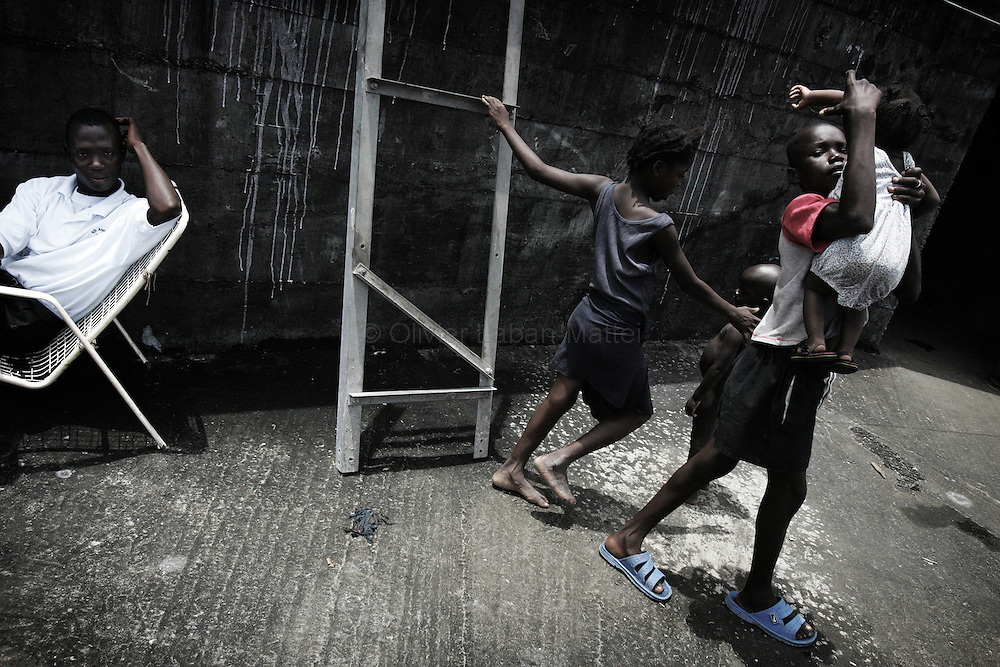 """A man sits while children play 19 September 2005 on the rooftop of the former uncompleted Ministry of National Defense building in Congo Town on the outskirts of Monrovia. The """"Pentagon"""", named this way by its occupants, shelters 394 families totalling approximately 3,000 people who were booted out in May 2005 of the Barclay Training Center, which had been their home for the last two decades. Former soldiers, who fought for former Liberian presidents Samuel Doe and Charles Taylor, live in this building with no water or electricity, overcoming past differences. The construction of the building started in 1984 under Doe's leadership, and the war interrupted the its completion and later served as a base for Taylor's men."""