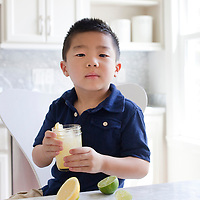 Child in kitchen with glass of Lemonade.