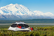 A woman sits in her tent with Mt. McKinley towering behind while camping in the backcountry of Denali National Park, Alaska.