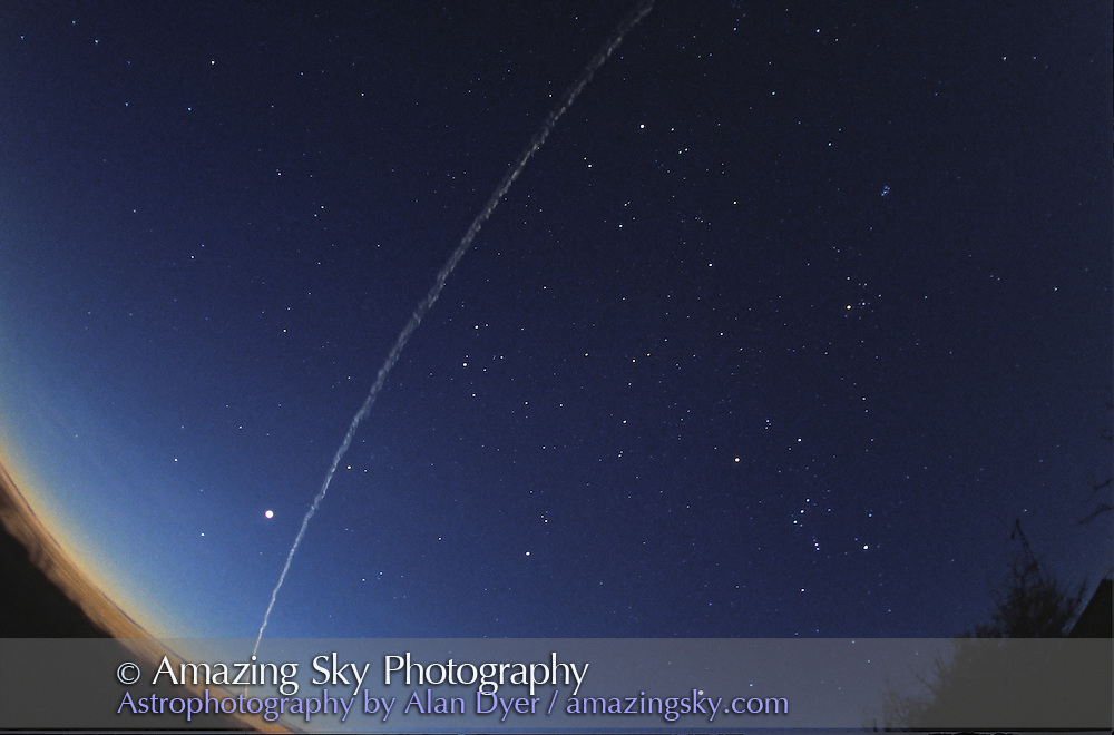 Re-Entry of Shuttle STS79 over southern Alberta, September 26, 1996 at dawn.<br /> <br /> Shuttle is gone here, moved off over Montana, leaving greenish train behind &mdash; the ionized &quot;smoke&quot; trail left by Shuttle. Train persisted for several minutes. Here it is spreading out.<br /> <br /> This image taken immediately after #3<br /> <br /> Orion and winter-fall sky constellations visible. Venus is bright object left of smoke train. <br /> <br /> 16mm full-frame fish-eye lens. Ektachrome 400 slide film. Untracked exposure for about 40 seconds.