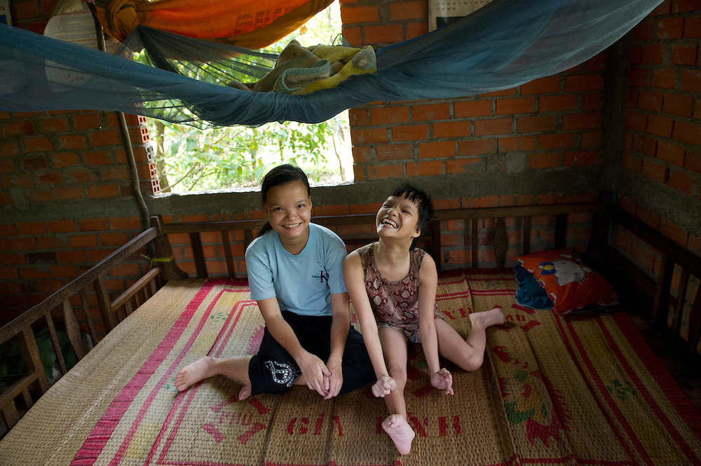 17 year old twin sisters, Tran Thu Nhuc Y and Tran Thu Vui  Mung (suffering from Dioxin poisoning) in the home they share with their family in Song Phu Village, Ben Tre Provence, Vietnam.