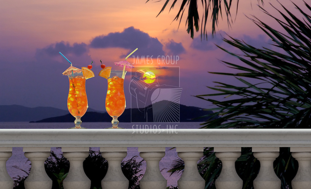 Two tropical fruit drinks with straws and umbrellas on a balcony with a tropical sunset in the background