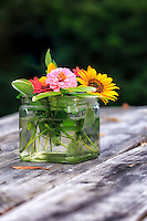 Bouquet of flowers in a jar, on a picnic table.