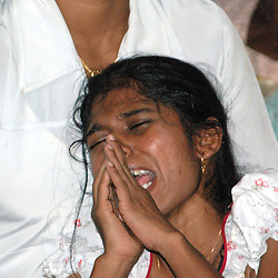 Sri Lanka, Kurunegala, 2006. A daughter lets go, her mother dead now at fifty. With two brothers to help, and a father passed away, the children must now fend for themselves.