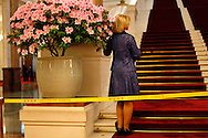 A guest to a celebration of the 99th Anniversary of the International Women's Day at the Great Hall of the People poses for a souvenir snap shot next to a flower pot in Beijing, China, Friday, March 6, 2009. The Great Hall of the people's with it's impressive Stalinist building style and attention to protocol remains as one of the the country's last showcases  of old style communism on a grand scale.