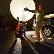 Daily Photo by Gary Cosby Jr.    UAH professor Kevin Knupp and a team of graduate and post-graduate students chase and study storms.  Danielle Kozlowski, kneeling, and Knupp hold onto a weather balloon the team is preparing to launch as it is filled with helium.