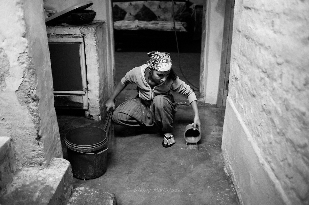 A young woman is cleaning the floor of her home in preparation of the upcoming Christmas celebrations. Living under poor conditions in the French colony slum, most Christians living there make a living as cleaners, sweepers or drivers for the wealthy people living in Islamabad