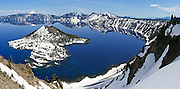 "The rim of the ancient exploded Mount Mazama volcano reflects in the deep blue lake at Crater Lake National Park, Oregon, USA. Snow covers most of Wizard Island. Published in ""Light Travel: Photography on the Go"" book by Tom Dempsey 2009, 2010. Panorama stitched from 3 images."