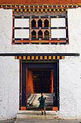 A boy emerges from the bridge to Trongsa Dzong, Bhutan.
