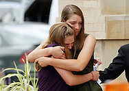 Two women embrace as the leave the memorial service for Gordon Cowdon at Pathways church in Denver July 25, 2012.  Cowden along with 11 others was killed in a shooting at a movie theater in Aurora, Colorado last Friday. The daughters are Kristian, Brooke and Cierra.  REUTERS/Rick Wilking (UNITED STATES)