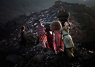 After bribing police, scavengers are allowed to illegally collect coal from a Bharat Coking Coal field February 19, 2010 in the town of Bokapahari in the Indian state of Jharkhand. Scavengers make about 40 Rupees(.90 USD) per basket of coal on the black market. Nearly 400,000 residents, 3000 in 400 homes in Bokapahari alone, live over dozens of giant underground coal fires that pump out toxic fumes and form fire pits underground that has lead to several deaths and collapsed homes. WIth coal scavengering a primary source of income for many residents, a proposed government relocation of residents is being met with resistance.