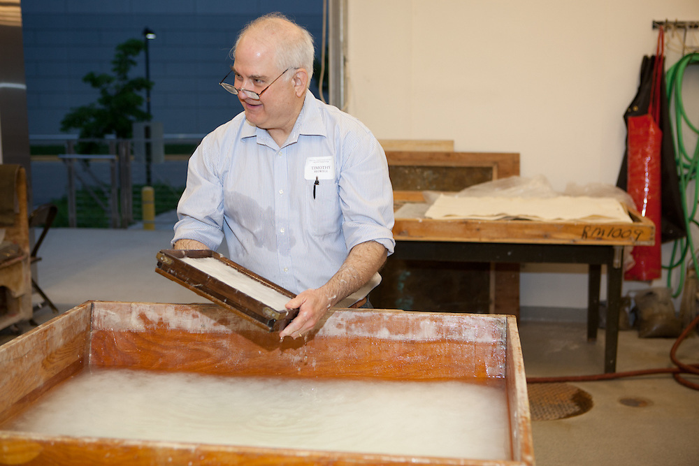 Timothy Howell is holding a mould and deckle with watermark from his father's (Douglas Howell) papermill.
