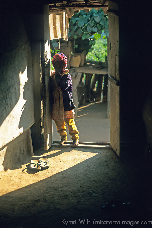 Asia, Nepal, Bardia. A young Tharu child in the doorway of her home in Bardia, Nepal.
