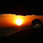 Crystal ball at sunrise, sunset under a deadfall of wood on Jekyll Island beach