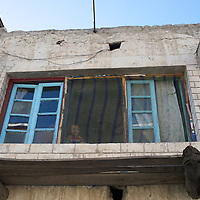 A young child peers through the window of home, Kargil