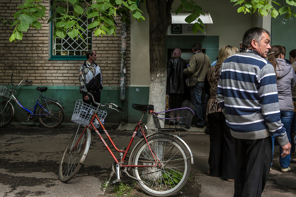 SLOVYANSK, UKRAINE - MAY 6:  People wait in line to withdraw money from a cash machine on May 6, 2014 in Slovyansk, Ukraine. Tensions in Eastern Ukraine are high after pro-Russian activists seized control of at least ten cities and ahead of the Victory Day holiday and a planned referendum on greater autonomy for the region. (Photo by Brendan Hoffman/Getty Images) *** Local Caption ***