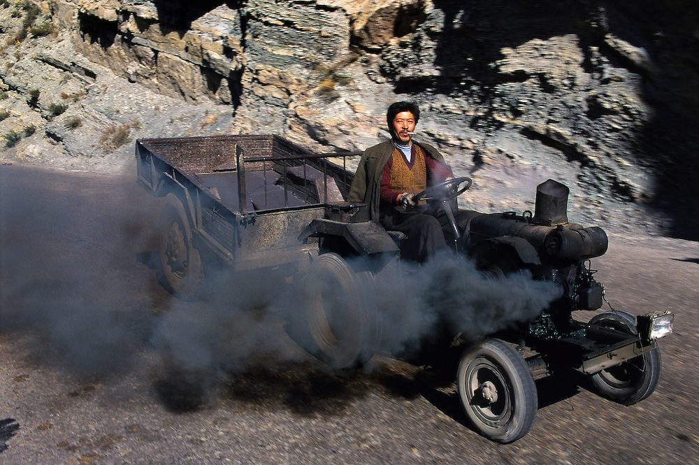 Pollution. Environment. Tractor driver in the Heng Shan mountains, going home after delivering a load of coal to a nearby town...From China [sur]real © Mark Henley..