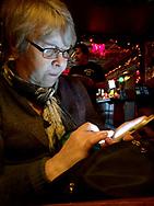 Senior woman using iPhone 7 plus in restaurant.