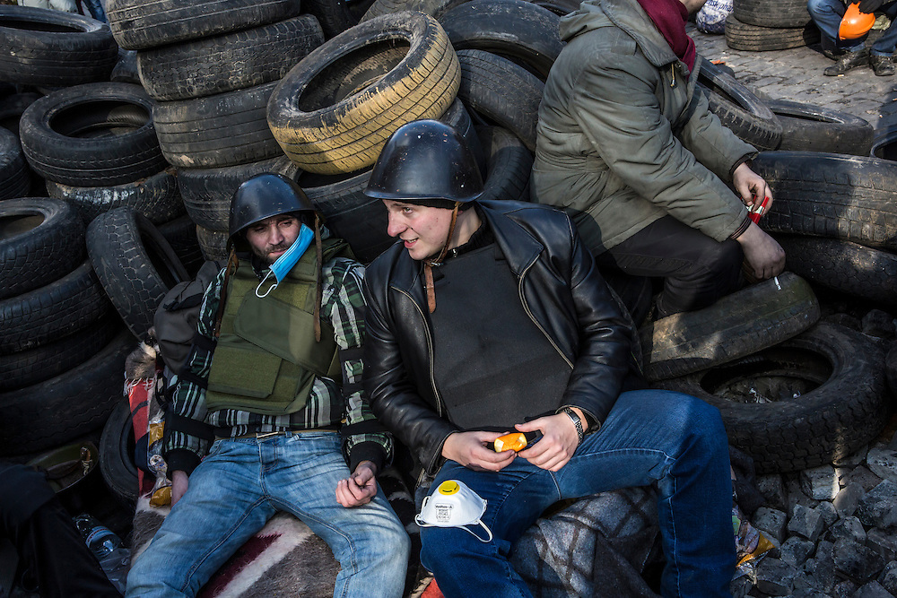 KIEV, UKRAINE - FEBRUARY 21: Anti-government protesters relax amid barricades made of tires Independence Square on February 21, 2014 in Kiev, Ukraine. After a week that saw new levels of violence, with dozens killed, opposition and government representatives reached an agreement intended to resolve the crisis. (Photo by Brendan Hoffman/Getty Images) *** Local Caption ***