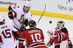 Apr 7; Newark, NJ, USA; New Jersey Devils goalie Martin Brodeur (30) reaches for the puck with his glove while New Jersey Devils defenseman Peter Harrold (10) and Ottawa Senators left wing Kaspars Daugavins (23) battle for the rebound during the third period at the Prudential Center. The Devils defeated the Senators 4-2.