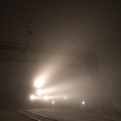 It's headlight cutting through extremely dense fog, a Metra Heritage Corridor train pulls into the depot at Joliet, IL.