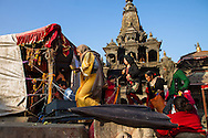 Worshipers perform puja, a Hindu act of devotion, at the ruins of the Char Narayan temple in Patan Durbar Square. The 17th century temple, sacred to Vishnu and one of the oldest at the World Heritage site, was destroyed in the earthquake. Devotees placed a tarp above the Vishnu idol, which remained in place after the wooden pagoda above it collapsed.