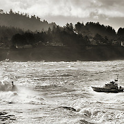 A Coast Guard rescue boat enters the harbor at Depoe Bay on the Oregon Coast, in stormy weather