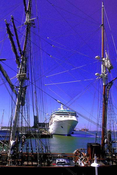 Cruise ship seen between a sailboats masts