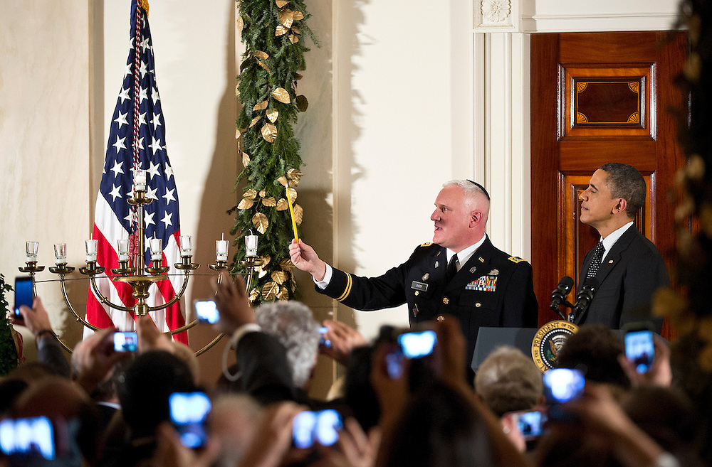 U.S. President Barack Obama watches as Rabbi Larry Bazer, Joint Force Chaplin for the Massachusetts National Guard, lights a menorah on the the sixth night of Hanukkah at the White House in Washington on December 13, 2012.      REUTERS/Joshua Roberts    (UNITED STATES)